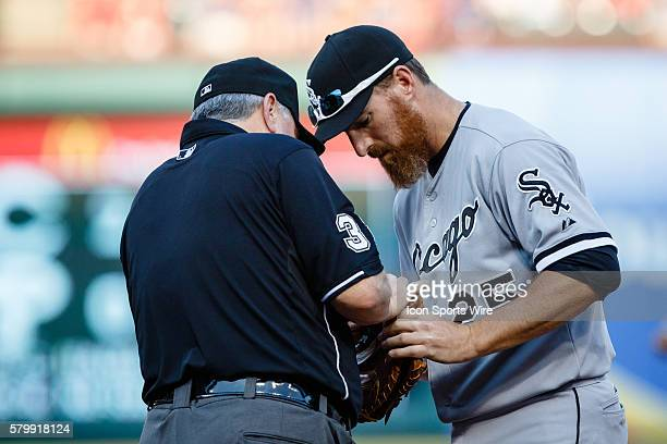 Chicago White Sox first baseman Adam LaRoche [3272] and first base umpire Dana DeMuth fix Adam's glove during the MLB game between the Chicago White...