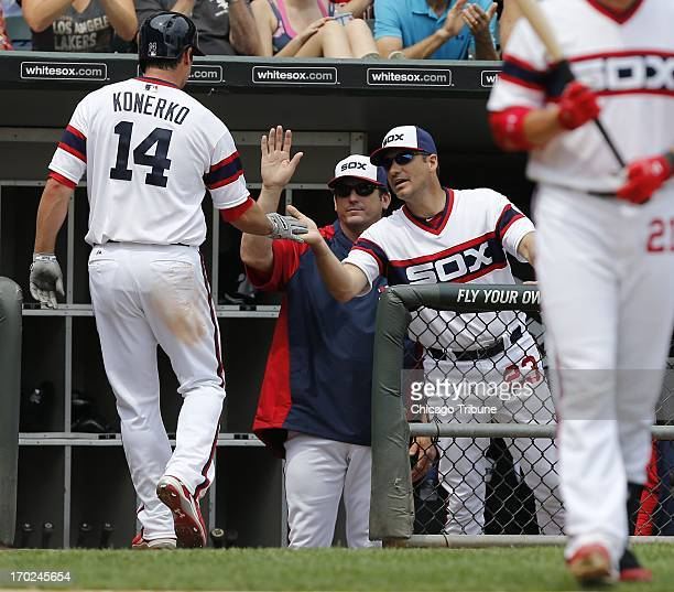 Chicago White Sox first baseman Paul Konerko is greeted by Chicago White Sox batting coach Jeff Manto middle and Chicago White Sox manager Robin...