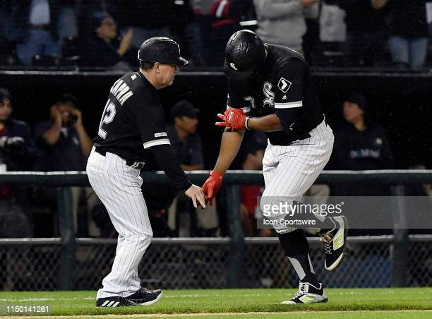 Chicago White Sox left fielder Eloy Jimenez celebrates with Chicago White Sox third base coach Nick Capra after hitting a three run home run in the...