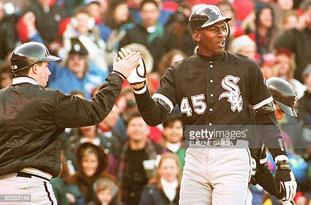Chicago White Sox outfielder Michael Jordan is greeted by a unidentified batboy at Chicago's Wrigley Field 07 April 1994 after scoring on a sixth...
