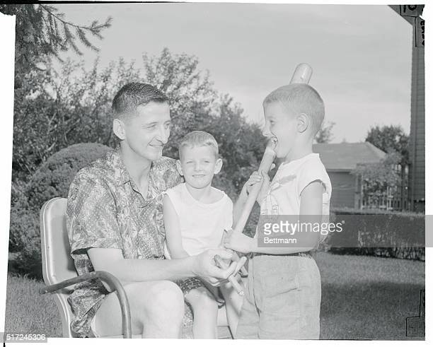 Chicago White Sox pitcher Dick Donovan offers batting tips to his nephew Bobby Kelley while 4 year old Jimmy likewise a nephew watches Dick relaxing...