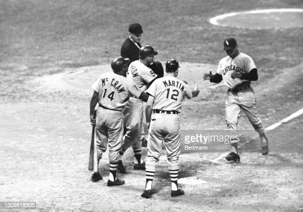 Chicago White Sox pitcher Juan Pizarro is congratulated by teammates Bill Skowron , J.C. Martin , and Tommy McCraw as he reaches home plate after...