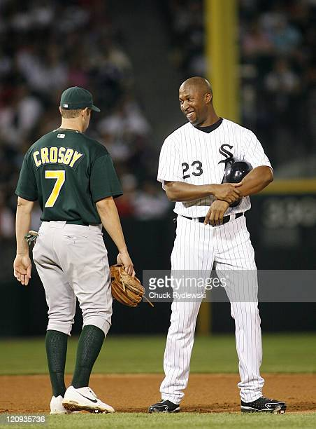 Chicago White Sox' Right Fielder Jermaine Dye shares a laugh with former teammate Bobby Crosby while the Athletics change pitchers during their game...