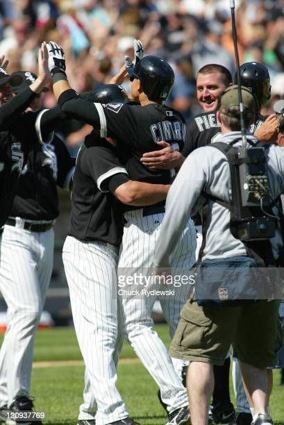 Chicago White Sox' second baseman Alex Cintron is mobbed at home plate after singling in the winning run against the Houston Astros June 24 2006 at...