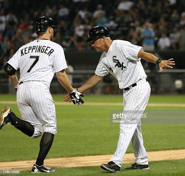 Chicago White Sox second baseman Jeff Keppinger is congratulated by Chicago White Sox third base coach Joe McEwing after his solo home run against...