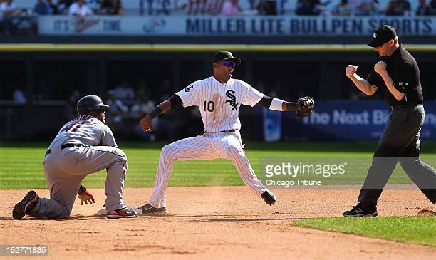 Chicago White Sox shortstop Alexei Ramirez looks to the umpire to see that he has tagged out the Cleveland Indians' Carlos Santana left at second...