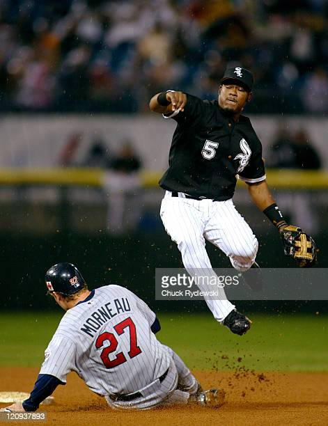 Chicago White Sox Shortstop, Juan Uribe, leaps to avoid a sliding Justin Morneau and turns a double play during the game against the Minnesota Twins...