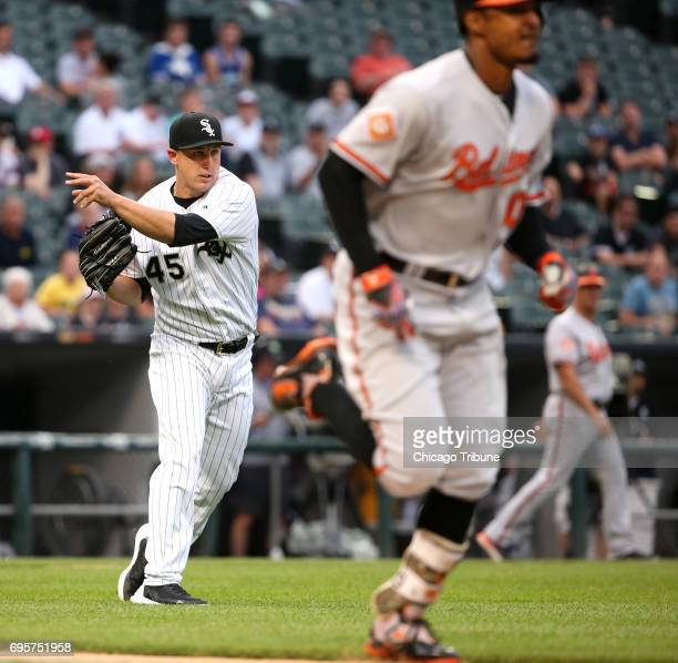 Chicago White Sox starting pitcher Derek Holland, left, throws to first base to get out Baltimore Orioles batter Adam Jones on a sacrifice bunt in...