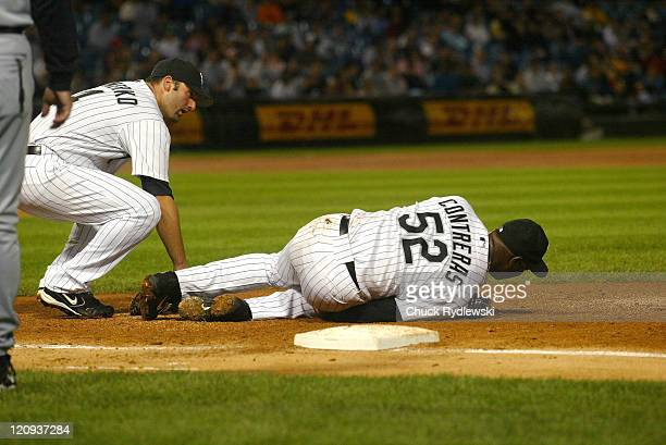 Chicago White Sox' Starting Pitcher Jose Contreras writhes in pain after pulling a hamstring covering 1st base during their game against the Seattle...