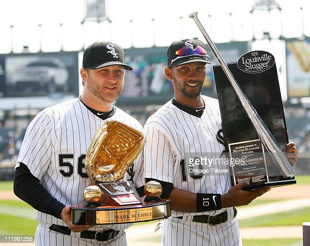 Chicago White Sox starting pitcher Mark Buehrle left is awarded the 2010 Gold Glove Award and Chicago White Sox shortstop Alexei Ramirez is awarded...