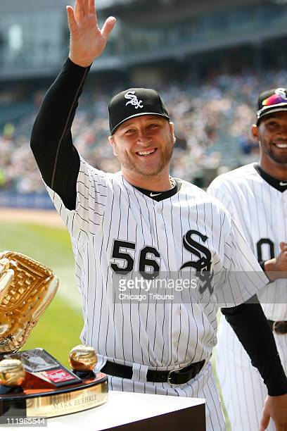 Chicago White Sox starting pitcher Mark Buehrle waves to the crowd after he receives his 2010 Gold Glove Award before a game against the Tampa Bay...