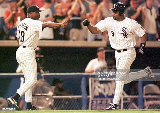 Chicago White Sox's Albert Belle is congratulated by third base coach Wallace Johnson after Belle hit a solo home run against the Cleveland Indians...