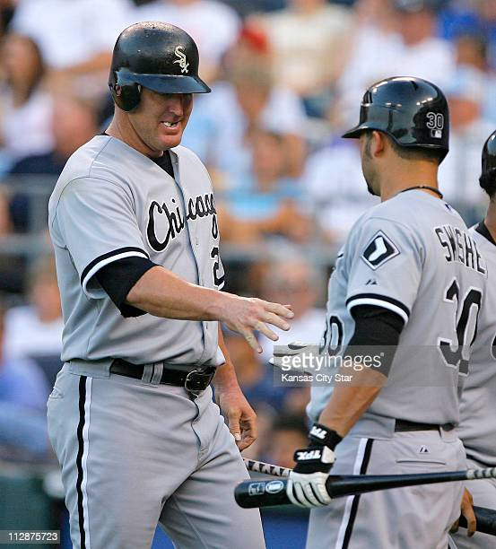 Chicago White Sox's Jim Thome left is congratulated by teammate Nick Swisher after scoring on an RBI single by Chicago White Sox's Ken Griffey Jr in...