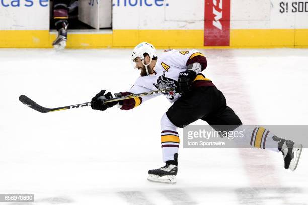 Chicago Wolves D Morgan Ellis fires the puck up the ice during the third period of the AHL hockey game between the Chicago Wolves and and Cleveland...