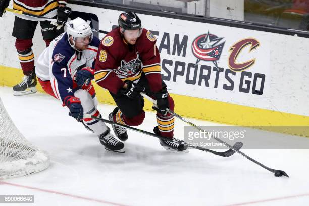 Chicago Wolves defenceman Griffin Reinhart controls the puck as Cleveland Monsters left wing Nick Moutrey defends during the third period of the...