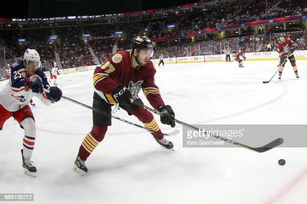 Chicago Wolves defenceman Jake Walman reaches for the puck as Cleveland Monsters center Alex Broadhurst defends during the second period of the...
