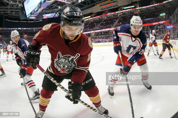 Chicago Wolves defenceman Kevin Lough attempts to dig the puck out of the corner as Cleveland Monsters center Sam Vigneault defends during the first...