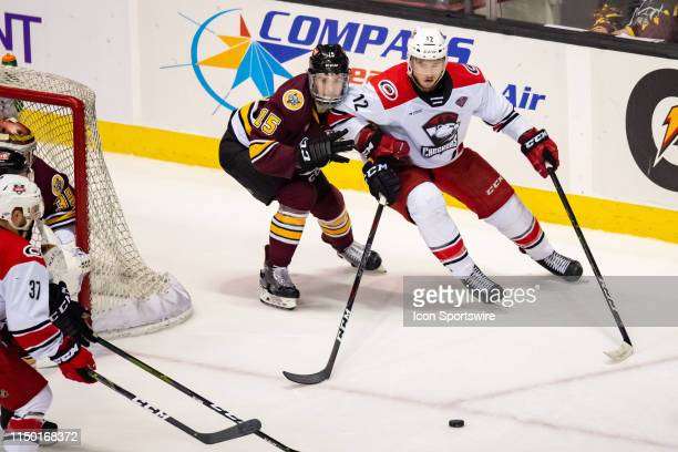 Chicago Wolves defenseman Dylan Coghlan and Charlotte Checkers right wing Julien Gauthier battle for the puck during game five of the AHL Calder Cup...