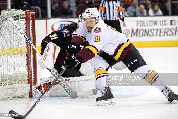 Chicago Wolves LW Andrew Agozzino reaches for the puck during the second period of the AHL hockey game between the Chicago Wolves and and Cleveland...