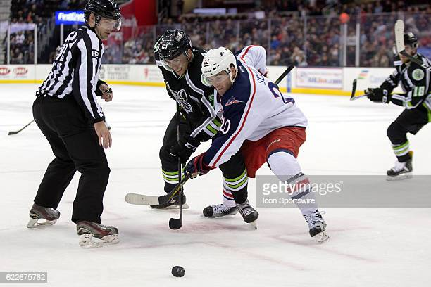 Chicago Wolves LW Magnus Paajarvi and Cleveland Monsters C Justin Scott battle for a faceoff during the third period of the AHL Hockey game between...