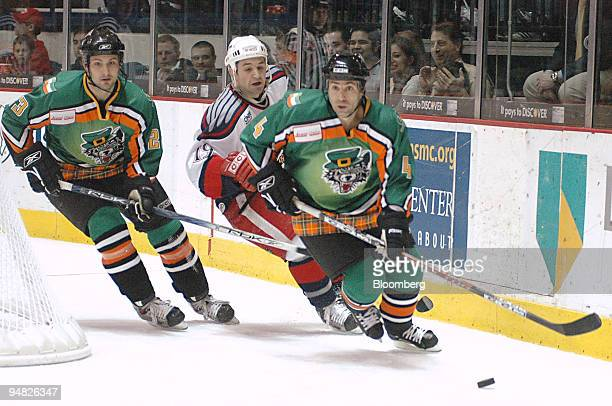 Chicago Wolves players Colin Stuart left and Bob Nardella far right are followed by Grand Rapids Griffins player Eric Himelfarb during a game at the...