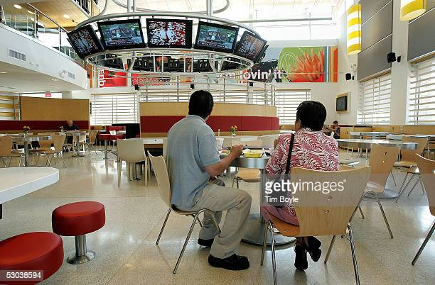 Chicagoans Jose Alcacio and his mother Sanjuana Alcacio eat their meal as they watch a bank of televisions inside a new McDonald's fastfood...