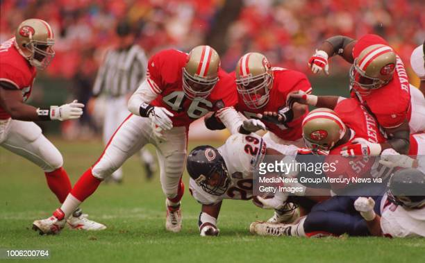 Chicago's Raymont Harris is swarmed by the Niners defenseTim McDonald Ken Norton Jr Dana Stubblefield and Bryant Young during first quarter action