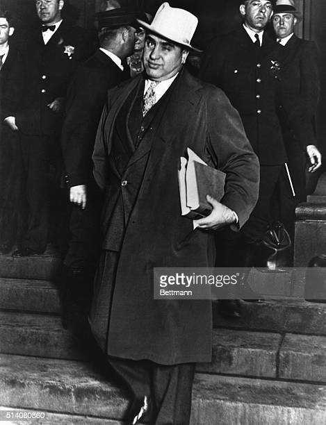 Chicago's vice overlord Al Capone winks to photographers as he leaves a Chicago courthouse on October 14, 1931 during in his case against the Federal...