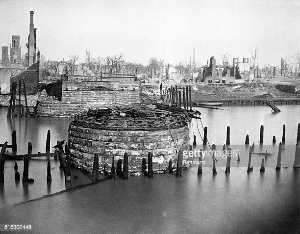 The famous Chicago fire of 1871 Photo shows the remains of a bridge apparently on a lake and some land rubble in the background The bridge's...