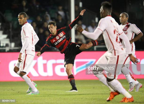 Chicharito of German club Bayer 04 Leverkusen kicks the ball between three defenders of Brazilian side Internacional to score his second goal of the...