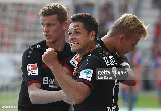Chicharito of Leverkusen celebrates with Joel Pohjanpalo after he scored his teams first goal during the Bundesliga match between Bayer 04 Leverkusen...