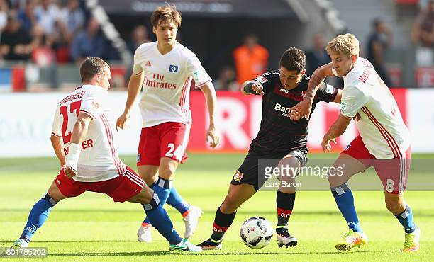 Chicharito of Leverkusen is challenged by Nicolai Mueller Gotoku Sakai and Lewis Holtby of Hamburg during the Bundesliga match between Bayer 04...
