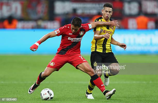 Chicharito of Leverkusen is challenged by Raphael Guerreiro of Dortmund during the Bundesliga match between Bayer 04 Leverkusen and Borussia Dortmund...