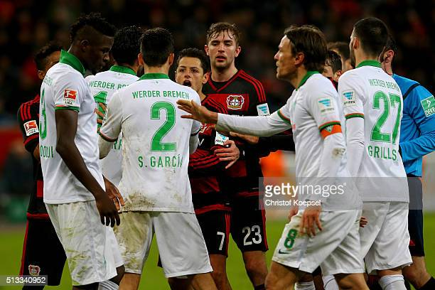 Chicharito of Leverkusen struggles with Santiago Garcia of Bremen during the Bundesliga match between Bayer Leverkusen and Werder Bremen at BayArena...