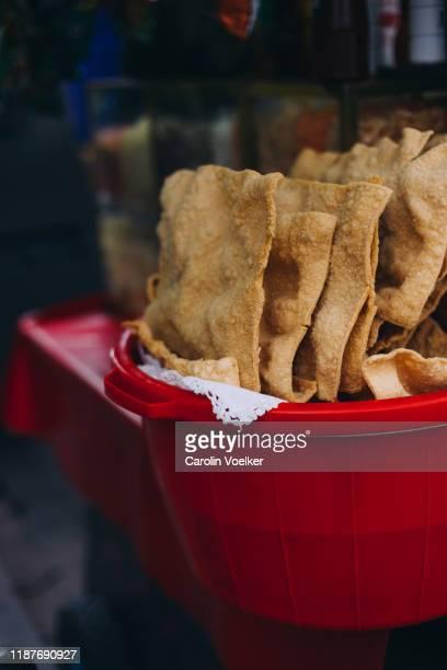 chicharrón (fried pork belly) in a red plastic tube - chicharrones fotografías e imágenes de stock