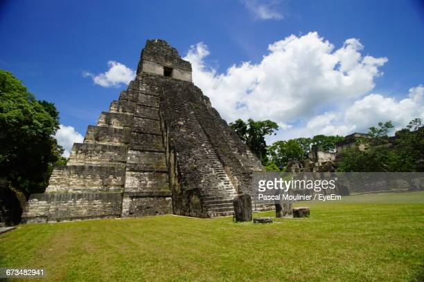 chichen itza against cloudy sky - kukulkan pyramid stock photos and pictures