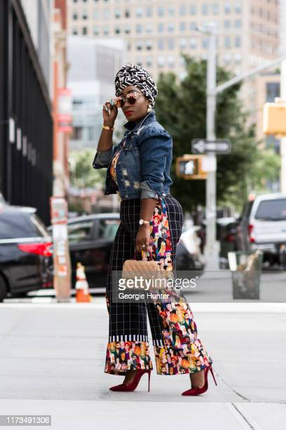 Chichi Amadi wearing black pants with face detail seam and hem, tan bag, denim jacket, floral sunglasses, black and white monochrome headscarf and...