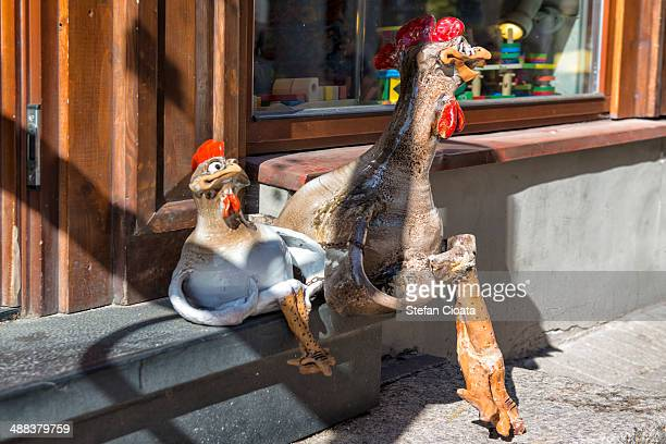a chicken and a rooster statues - funny rooster stock photos and pictures
