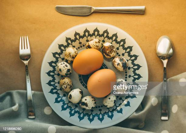 chicken and quail eggs on a plate with a gray ornament and metal cutlery; making breakfast at home, warm light - salmonella bacteria stock pictures, royalty-free photos & images