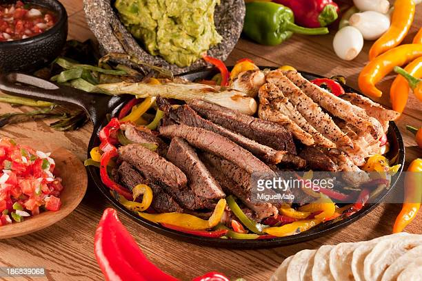 Chicken and steak fajita meat with peppers on skillet