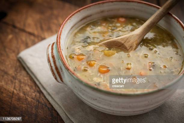 Chicken and vegetable soup in a rustic bowl against a dark wood background.