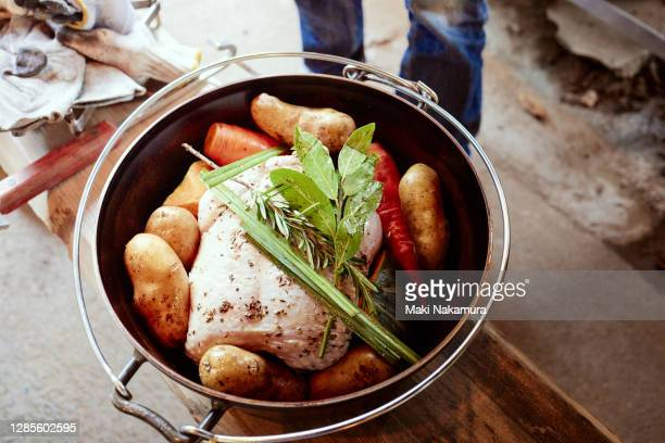 chicken and vegetables in a dutch oven to be cooked. - キャンプ 1人 ストックフォトと画像