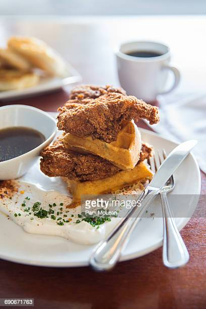 chicken and waffles with syrup and crème fraiche - chicken and waffles stock photos and pictures