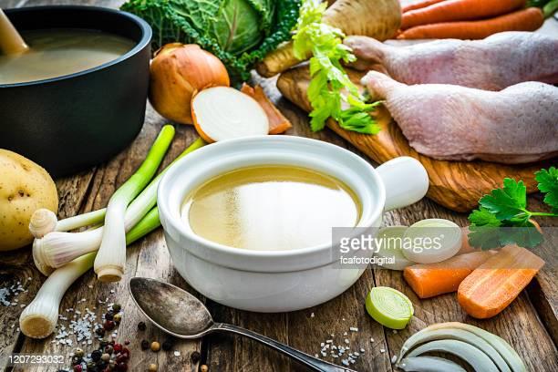 caldo de pollo en un tazón e ingredientes en la mesa de cocina de madera - caldo pollo fotografías e imágenes de stock