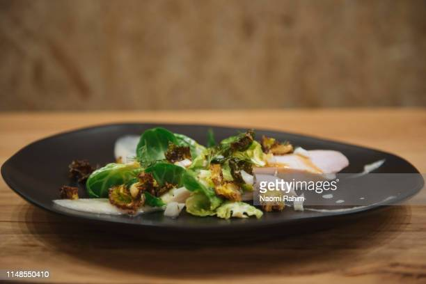 Chicken breast dish with brussels sprouts and horseradish sauce, served on trendy plate