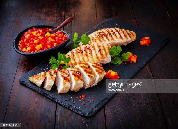 chicken breast fillet with bell pepper chutney on slate - poulet grillé photos et images de collection