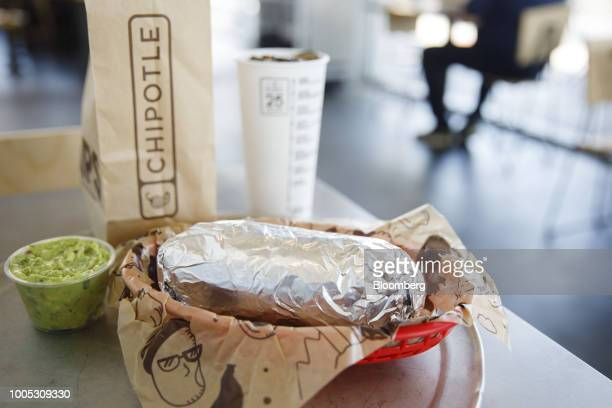 A chicken burrito guacamole bag of tortilla chips and a drink are arranged for a photograph at a Chipotle Mexican Grill Inc restaurant in El Segundo...