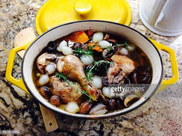 Chicken coq au vin braised in burgundy wine with mushrooms onions and carrots in a covered pot