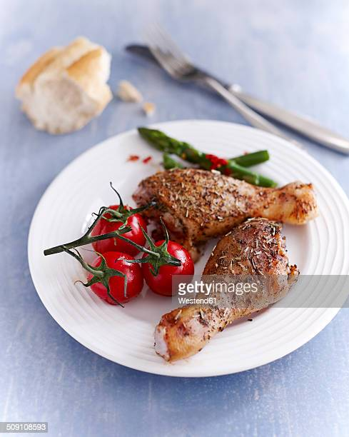 Chicken drumsticks on plate with tomatoes and asparagus