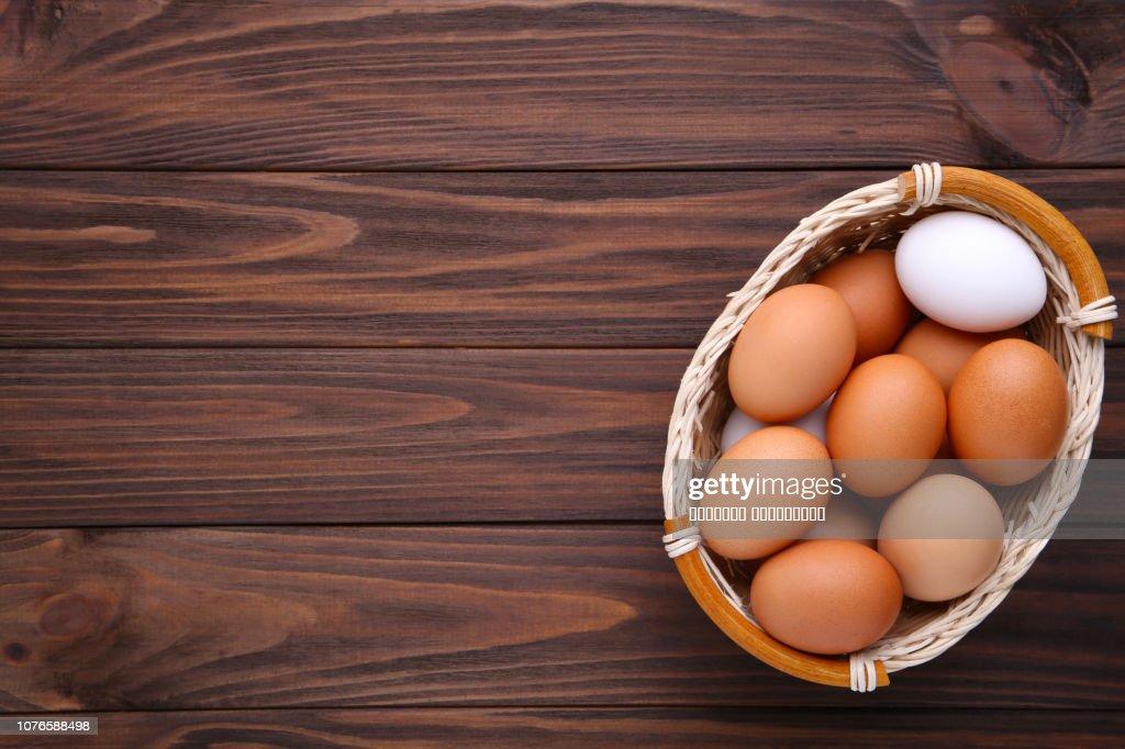 Eier im Korb auf braunem Holz Hintergrund : Stock-Foto